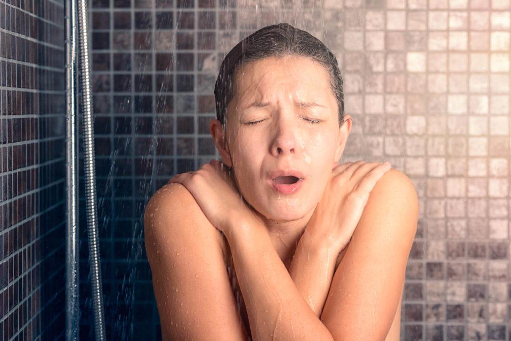 Frau friert unter der Dusche